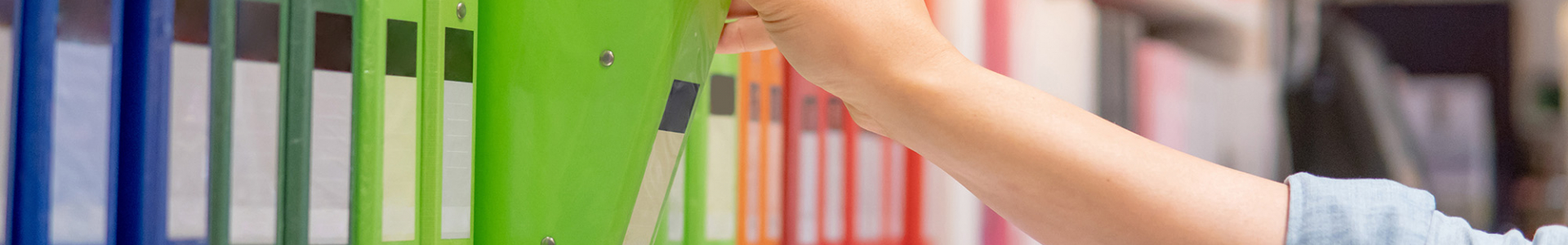 photo of someone grabbing a green binder off a shelf amidst other colorful binders