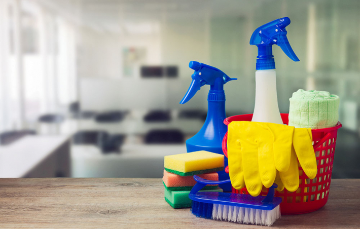 photo of a closeup of cleaning supplies and an office in the background