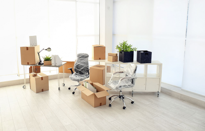 photo of a mostly empty room with a desk and some unopened boxes and wrapped office chairs in the corner