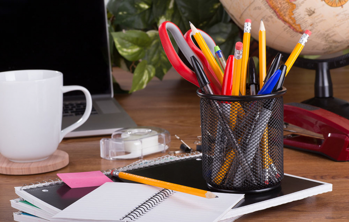 photo of a desk with a netted cup full of pens, pencils and a pair of scissors. there's a notebook underneath the cup with a few papers on top of that and a mug off to the left with a coaster underneath