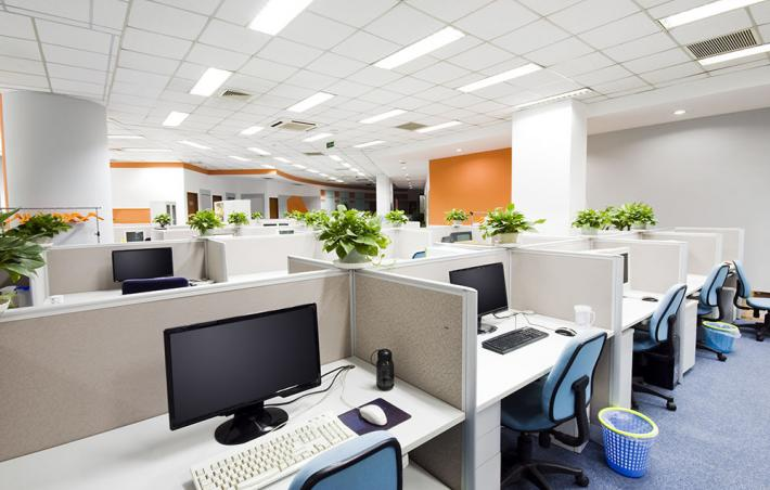 photo of an office with various cubbies with empty chairs and monitors
