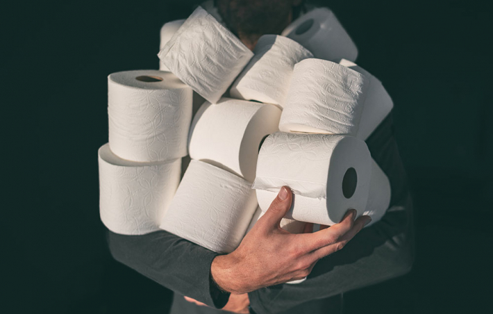 photo of someone holding a bunch of toilet paper rolls in their arms. their face is hidden behind the mound of tp