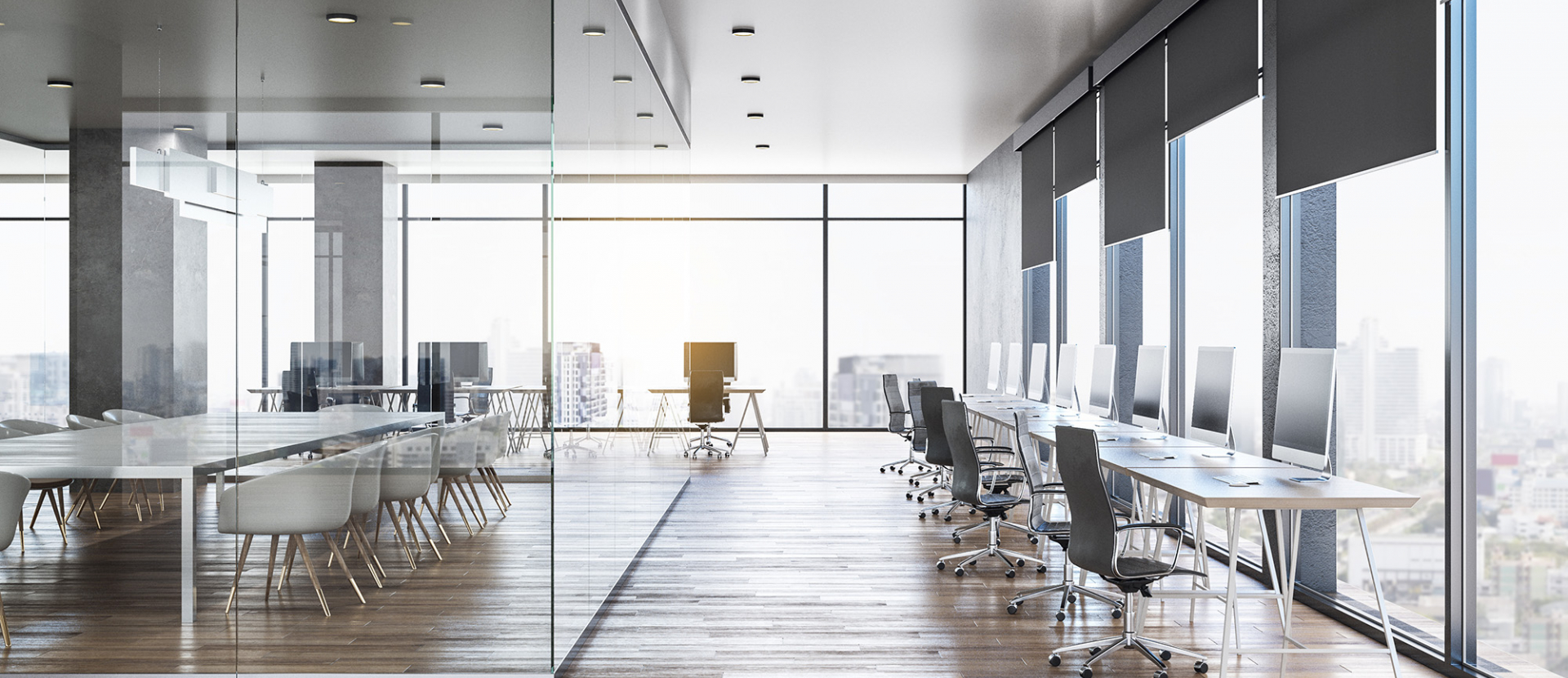 open, empty office space with glass walls and wooden floors. desks are lined up against the floor-to ceiling windows giving way for more space in between things